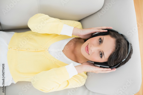 Smiling casual brunette in yellow cardigan listening to music wi