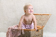 Joyful baby in a wicker chest