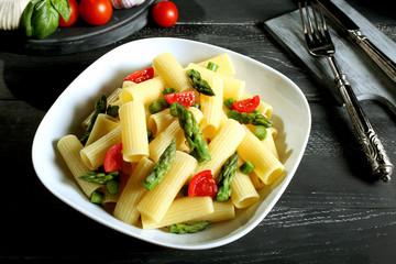 pasta maccheroni asparagi e pomodori sfondo grigio