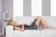 Casual blonde lying on couch using laptop