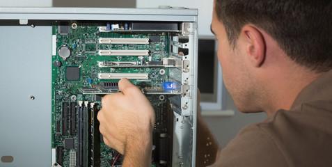 Computer engineer examining open computer