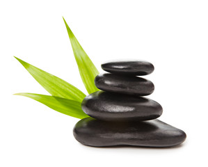 Zen concept - pyramid of black stones and bamboo leaves