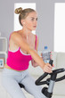 Sporty stern blonde training on exercise bike listening to music
