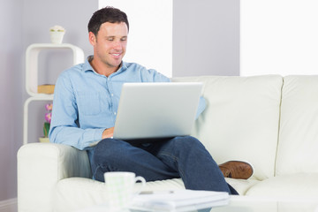 Content casual man sitting on couch using laptop