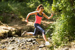Sporty young woman leaping over a stream