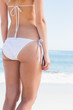 Rear mid section of toned woman in white bikini
