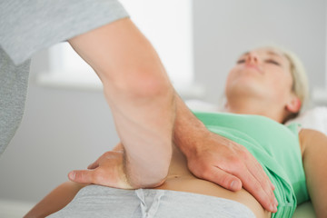Physiotherapist checking patients pelvis alignment