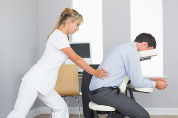 Masseuse treating clients lower back in massage chair
