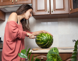 a girl is cutting watermelon