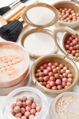 Women's cosmetics - powder, blush, brushes on the table