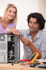 Woman watching her husband repair a computer