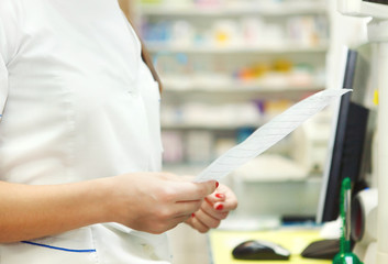 Pharmacist chemist woman with prescription in a drugstore
