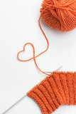 Incomplete knitting project with ball of orange wool poster