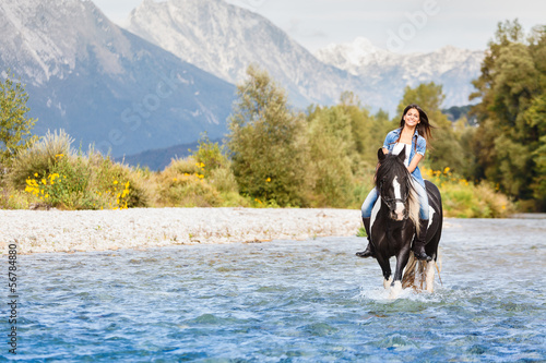 Smiling Female horse rider crossing river in a mountainous lands