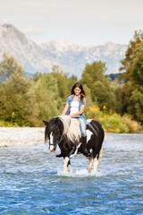 Beautiful Female sitting on horse while crossing river in a moun