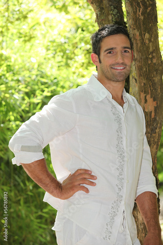 Man posing by a tree