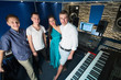 Three smiling guys musician and a girl singer in Studio