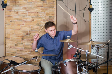 The drummer plays the drum kit in the studio