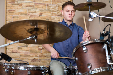 The young drummer plays the drum kit in the studio