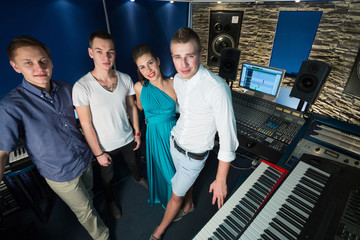 Three guys musician and a girl singer in Studio