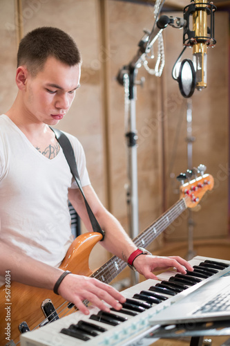 Musician with a guitar around his neck plays keyboards