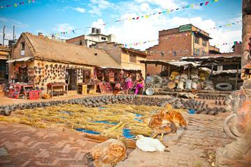 Nepalese craftswoman arranging pots in Bhaktapur, Nepal