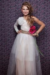 Portrait of smiling little beautiful girl posing in long dress