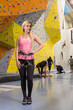 smiling girl stands with climbing equipment on climbing gym