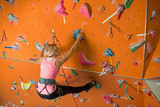 girl is engaged in rock climbing on climbing gym