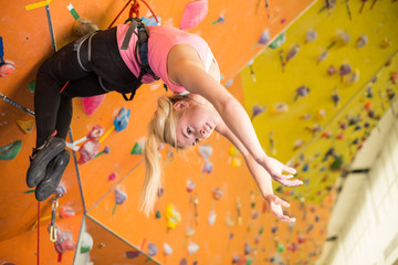 Girl with climbing equipment hanging on rope up face