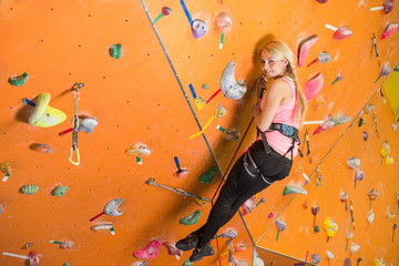 girl with climbing equipment hanging on rope on climbing gym