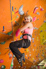 Woman with climbing equipment hanging on rope on climbing gym