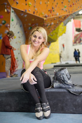 smiling girl sits with climbing equipment on climbing gym