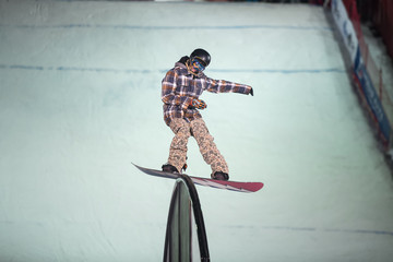 The guy in the plaid jacket snowboard slides on the rail