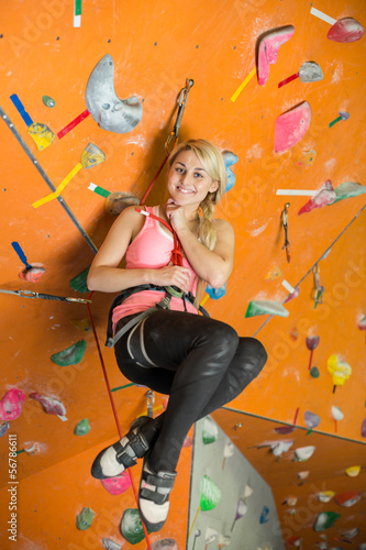 smiling girl is engaged in rock climbing on climbing gym