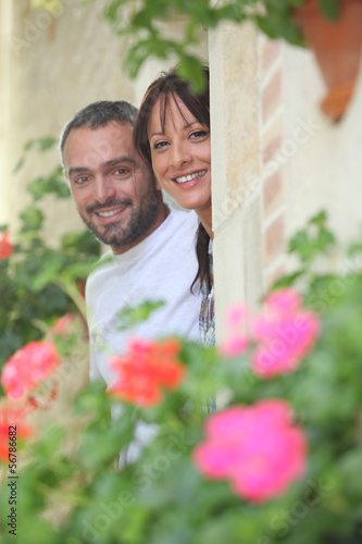 Couple hiding by a stone wall