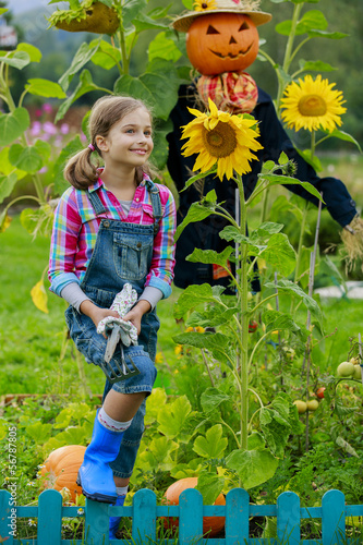 Scarecrow and happy girl  in the garden -  harvests