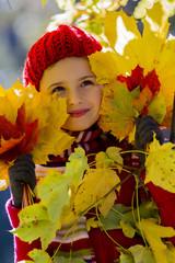 Autumn fun - lovely girl playing in autumn park