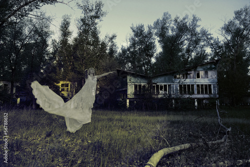 The ghost is flying on the background of an abandoned building