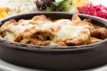 Cheese melted on chicken casserole in terracotta plate