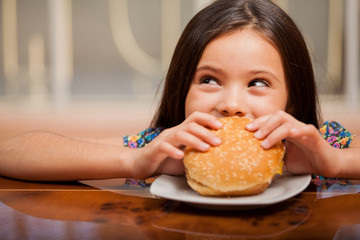 Little girl eating a hamburger