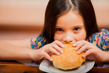 Portrait of a little girl biting a cheeseburger at home