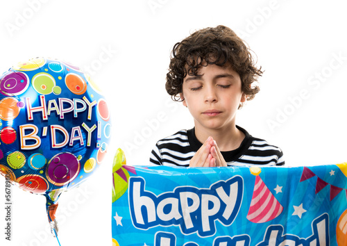 Hispanic child praying before his birthday party