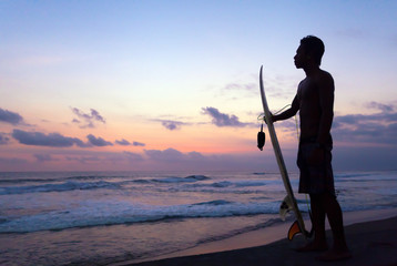 Indonesian surfer standing at sunset in Ocean in Bali, Indonesia