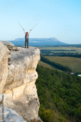 Smiling young woman standing on the top of mountain