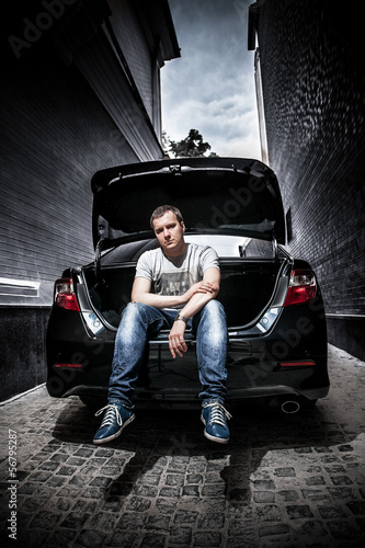 Handsome man sitting in car trunk