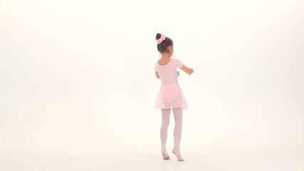 Little ballet dancer performing ballet pas in a studio