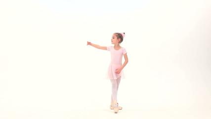 Little ballerina posing in a studio
