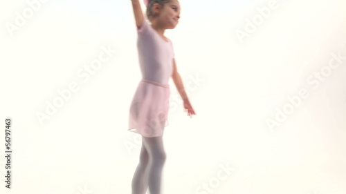 Little ballet girl performing in a studio