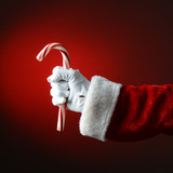 Santa Claus Holding Large Candy Cane over a Light to Dark Red Ba